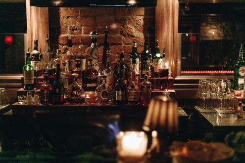 a photograph of the alcohol bottles behind a bar